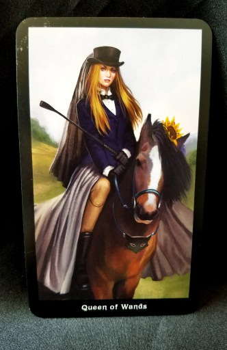 Queen of Wands Tarot - A confident woman in riding apparel seated on a horse