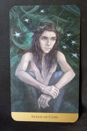 Seven of Cups - A youth seated in a contemplative pose, seven stars twinkling around his head