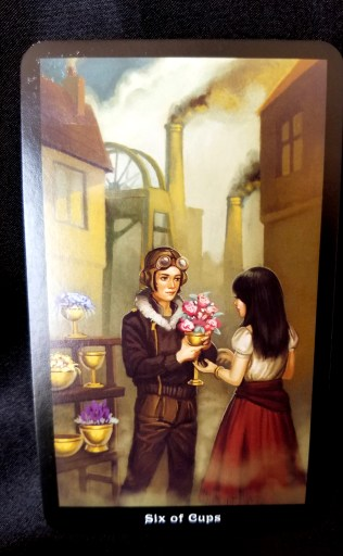 Six of Cups Tarot Card - A young man dressed as an aviator given a young woman flowers in a cup