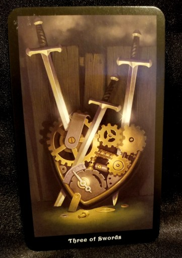 Three of Swords Tarot Card - A heart made of gears with three swords piercing it.