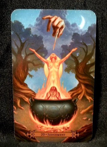 Judgement - Tarot Card: a woman standing over a man in a cauldron which is over the flames. A hand with a wands is pointing at the woman