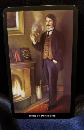 King of Pentacles - Tarot Card:  A handsome, well-dressed, wealthy man smoking a pipe is standing in front of a roaring fire.