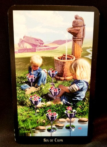 Six of Cups - Tarot Card: Two cholderen sitting next to a stream placing flowers into six silver cups