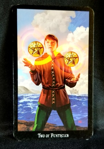 Two of Pentacles - Tarot Card:  A young man juggling two pentacle discs.  As he juggles an infinity loop is created.