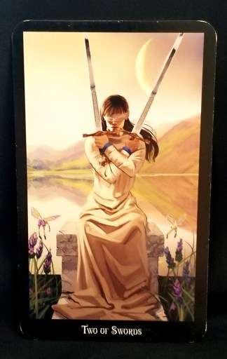 Two of Swords - Tarot Card:  A young women sitting on a stone bench.  She is blindfolded, holding swords in both hands, armed crossed over her chest.