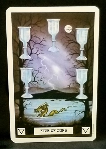 Five of Cups - Tarot Card:  A water dragon swimming in a lake under a stormy sky.  Five silver chalices frame the picture.