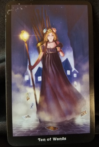 Ten of Wands - Tarot Card: A young woman carrying a lighted staff, nine more wands in a pack on her back. Tarot cards are drifting around her feet.