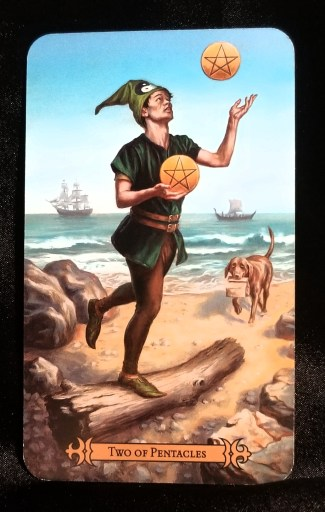 Two of Pentacles - A young man balacing on one foot while standing on a log and juggling two pentacle discs.  A dog carrying a bag is moving towards him.