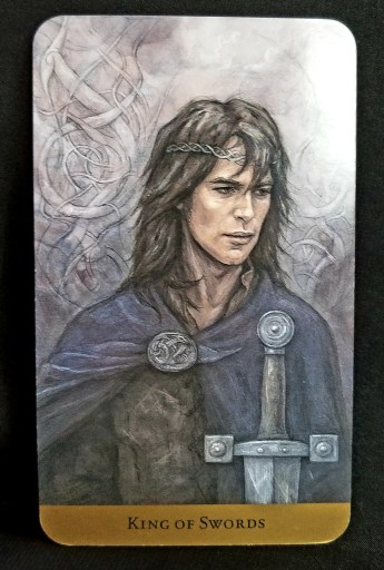 King of Swords - Tarot Card: An authoritative man wearing a crown and dressed in a cloak.  He holds a sword and is lookijng towards the future.