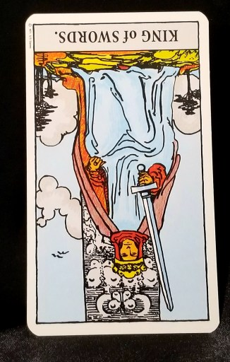 King of Swords, Reversed - An upside down tarot card depicting a king seated on his throne holding a sword.