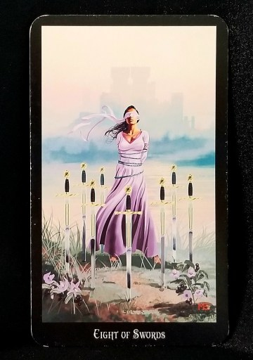 Eight of Swords - Tarot Card:  A blindfolded and bound woman standing in a circle of eight swords.