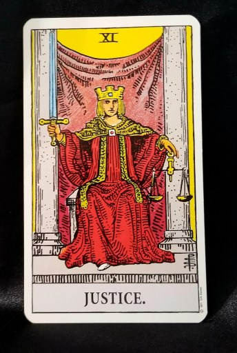 Justice: A King seated upon a throne,  He is holkding a sword upright in his right hand and a set of scales in his left.
