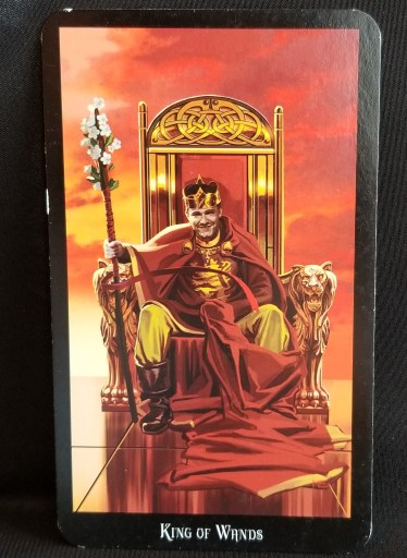 King of Wands- A King dressed in red and gold sitting atop a throne. He holds a flowered wand.