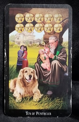 Ten of Pentacles - An older man holding an infant while a dog rests at his feet.  The child's parents look on from the background.