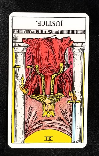 Justice: Reversed - a udge seated on a throne.  The card is upside down