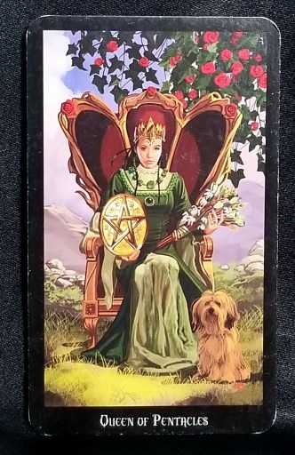 Queen of Pentacles - a beautiful woman dressed in green, holding a bouquet and pentacle disc.  A fluffy dog sits at her feet.
