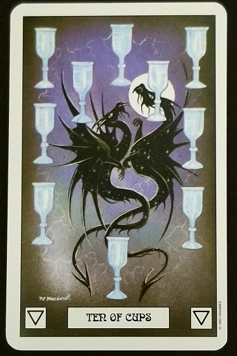Ten of Cups - Two black dragons face each other . They are surrounded by 10 silver chalices - a full moon behind them.