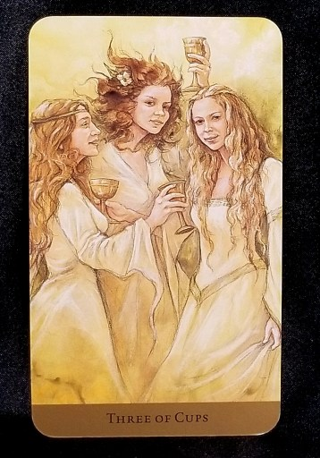 Three of Cups - Three beautiful young women with smiles on their faces are holding cups and toasting each other.