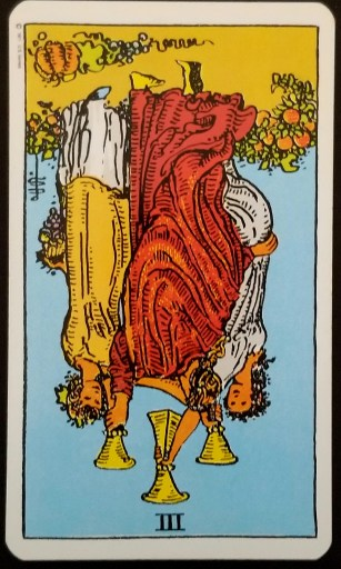 Three of Cups, Reversed - Three maidens holding cups aloft.  The card is upside down.