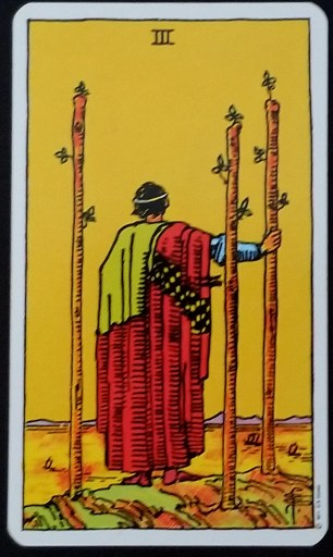 Three of Wands - A man looking over a his ships sailing on the sea. Three staves surround him.