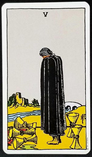 Five of Cups- A cloaked figure stands dejectedly.  Three fallen cups are in front of him, two standing up behind.