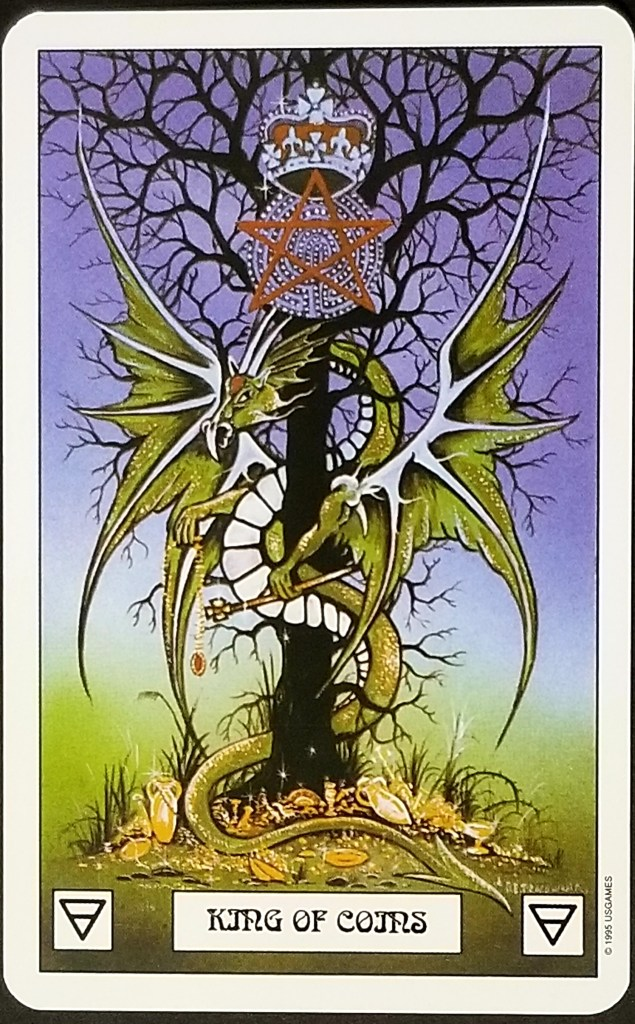 King of Coins - A large green dragon isf curled around a tree.  A large pnetacle is beneath a crown at the top of the tree.