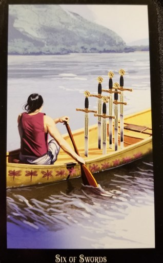 Six of Swords -  Tarot Card:  A  woman paddling a canoe with six swords stuck upright into the hull.