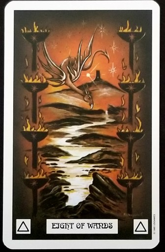 Eight of Wands- A red dragon hovers over a lake.  Eight torches flank it on each side.