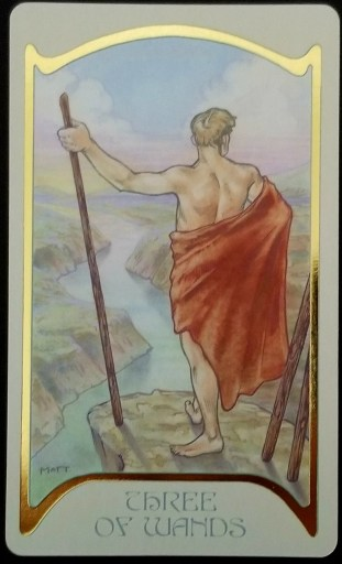Three of Wands- A man in a toga leans on a staff while standing at a cliffs edge.  He looks over a river valley.