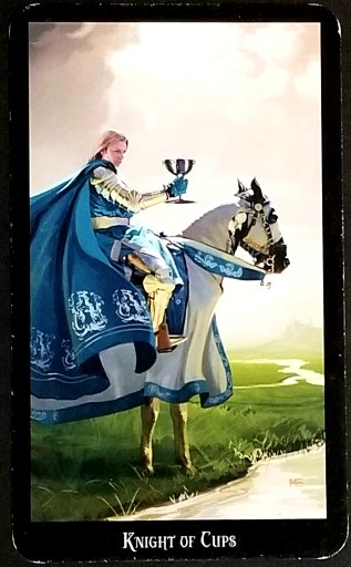 Knight of Cups- Tarot Card: A gallant knight holding a silver chalice sits atop a horse.