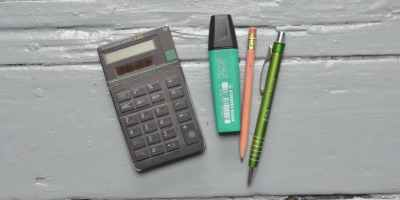 calculator near stationery on white table