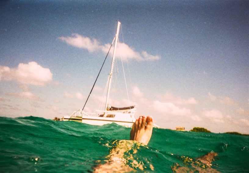 man underwater with white yacht beside