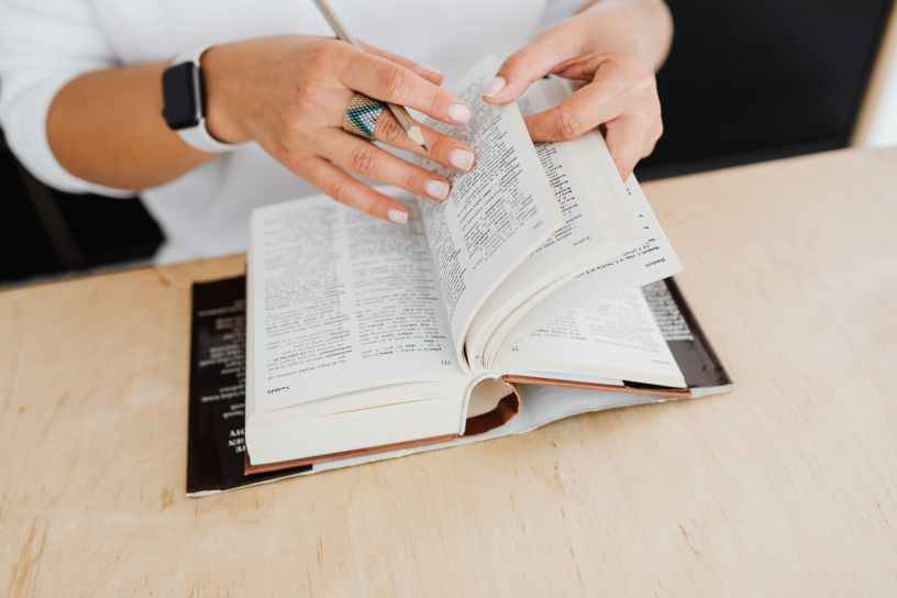 person wearing silver ring holding white book page