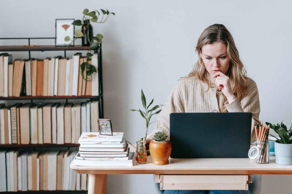 pensive woman browsing laptop near books