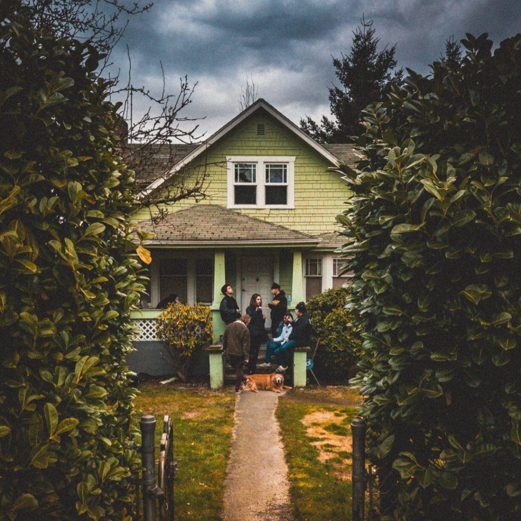 Portal de casa al fondo de un jardín con amigos conviviendo y un perro echado al frente.