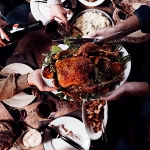 Una mesa donde hay platos y copas en la parte del fondo, y en primer plano unas manos se pasan un platón con un pollo rostizado.