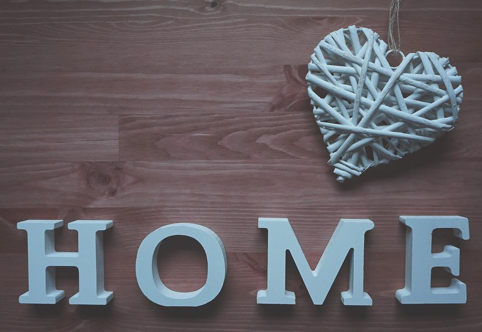 """Sobre fondo de madera la palabra """"HOME"""" hogar en ingles y un corazón trenzado ambos en blanco."""