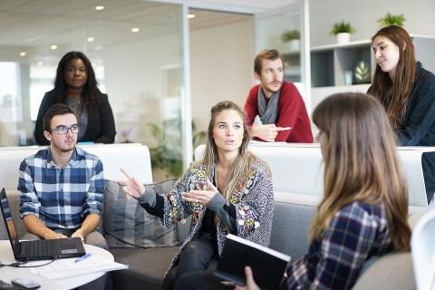 Mujeres y hombres en un espacio de reunión en una oficina, realizando una reunión y compartiendo puntos.