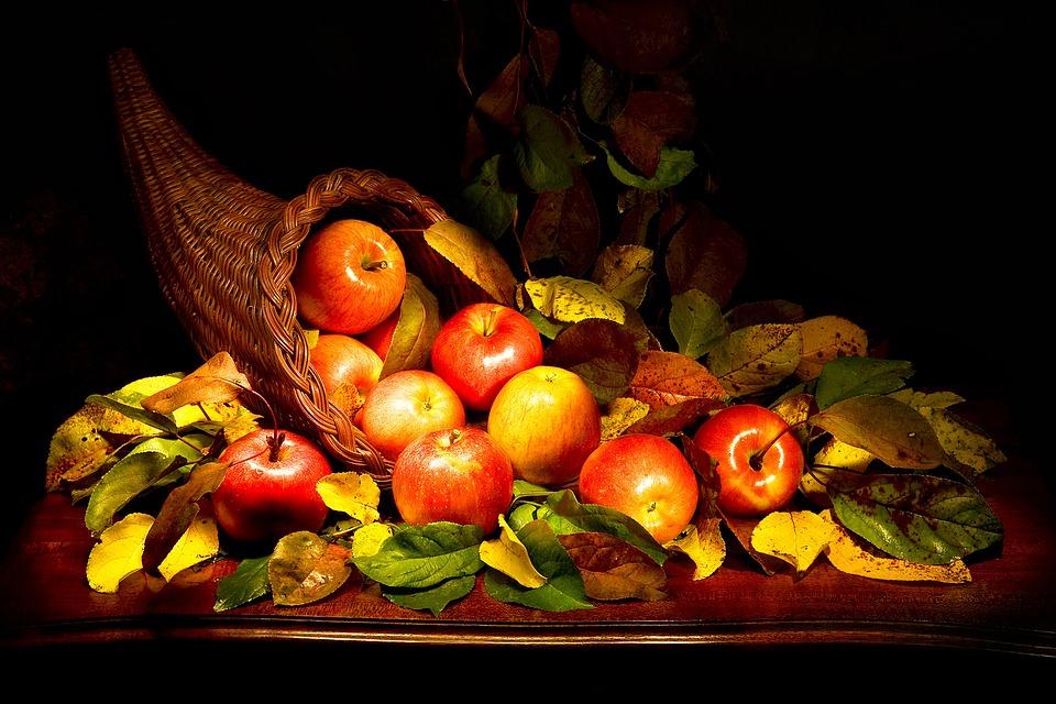 Cuerno de la abundancia sobre una mesa. Con manzanas y hojas.