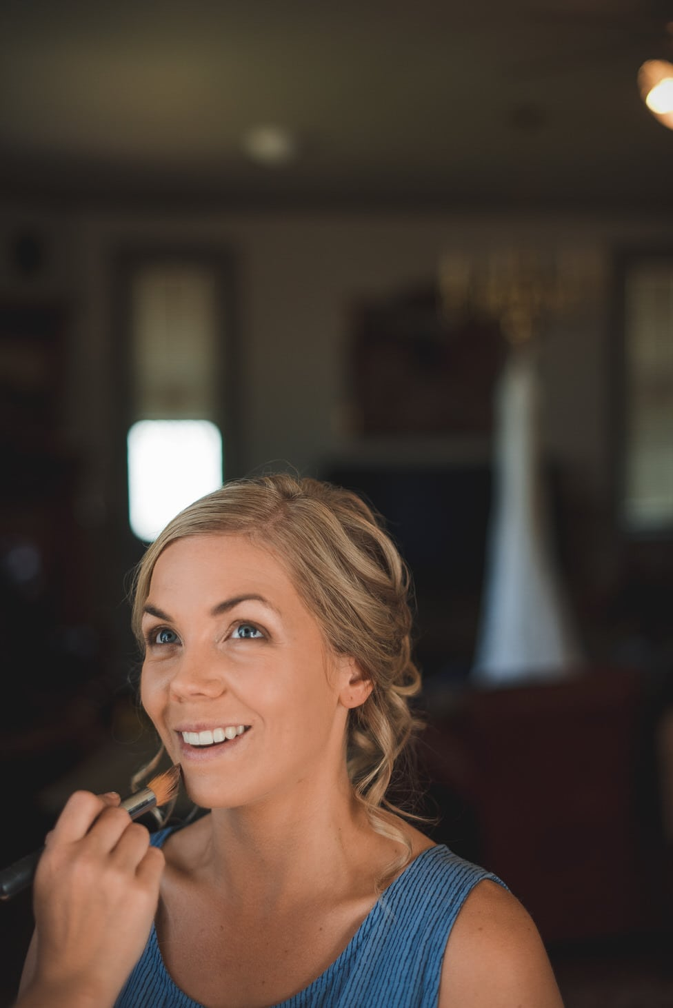 bride's makeup is applied with dress hanging in background