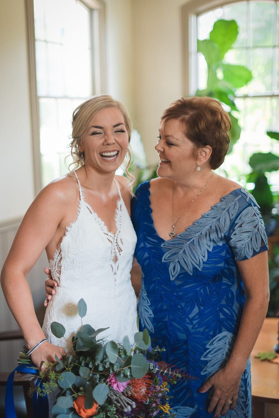 bride laughs with mother of the bride in blue dress