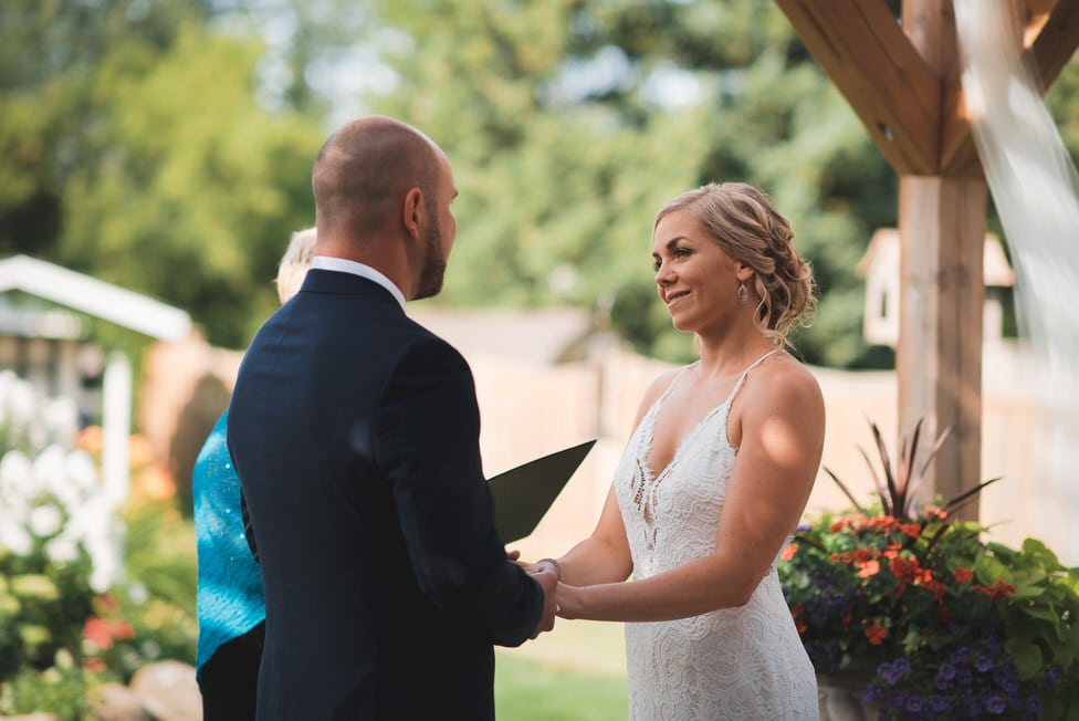 bride and groom make eye contact during backyard wedding ceremony