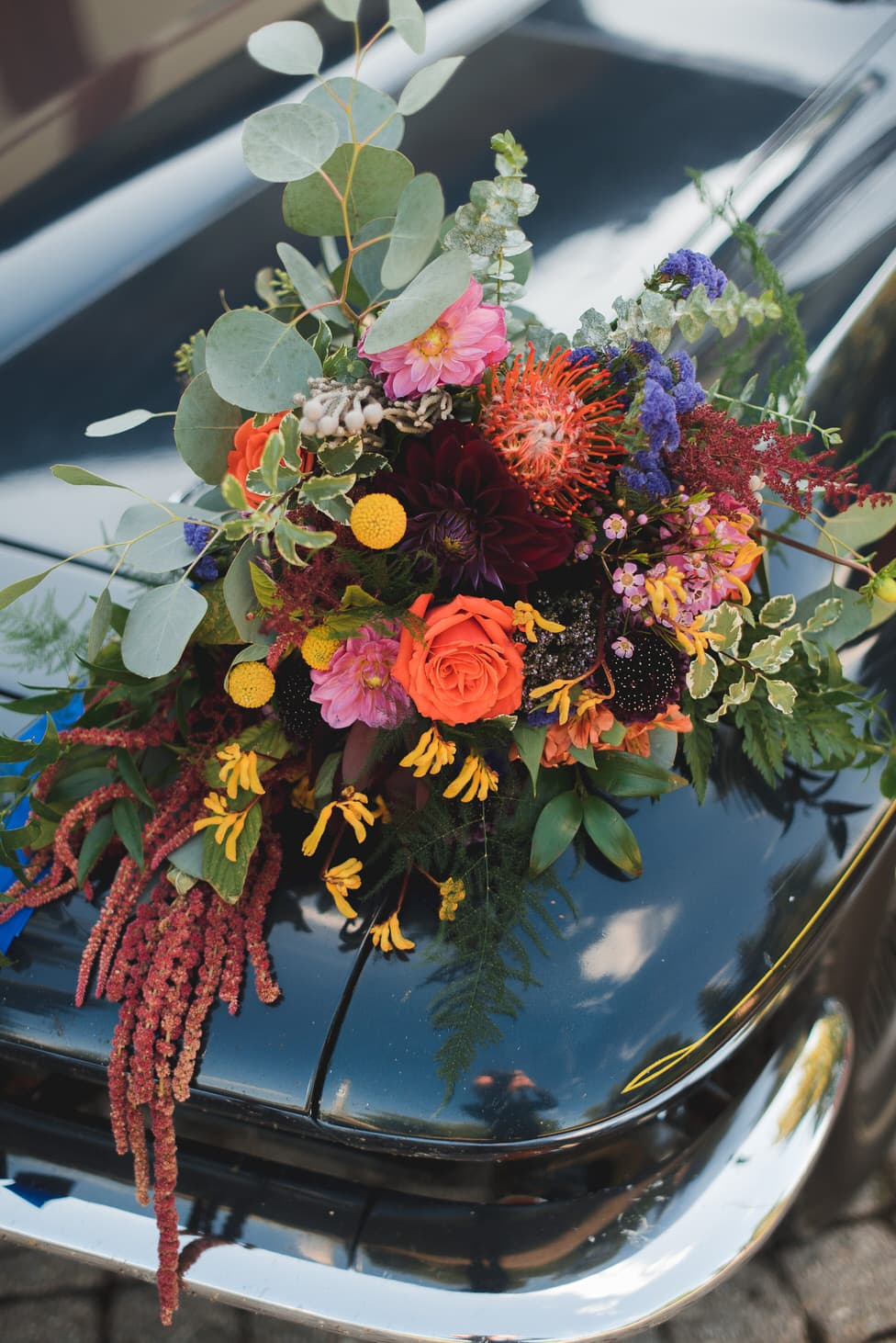 bridal bouquet sits on the hood of an antique car, designs by cate stratford