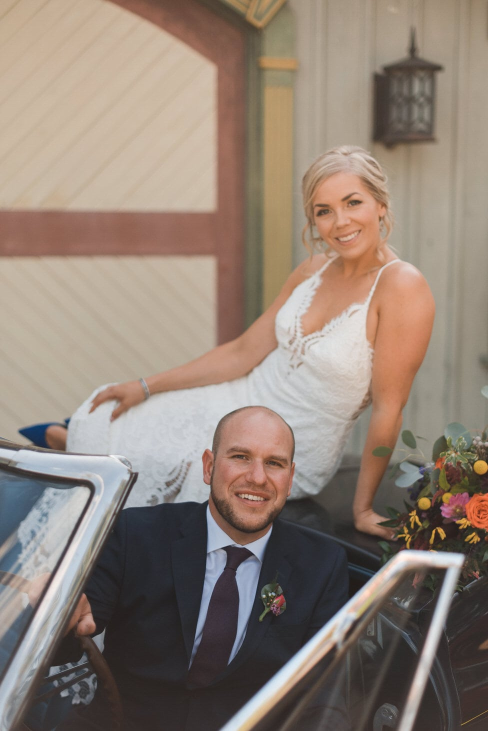 bride sits atop antique convertible with groom in driver's seat