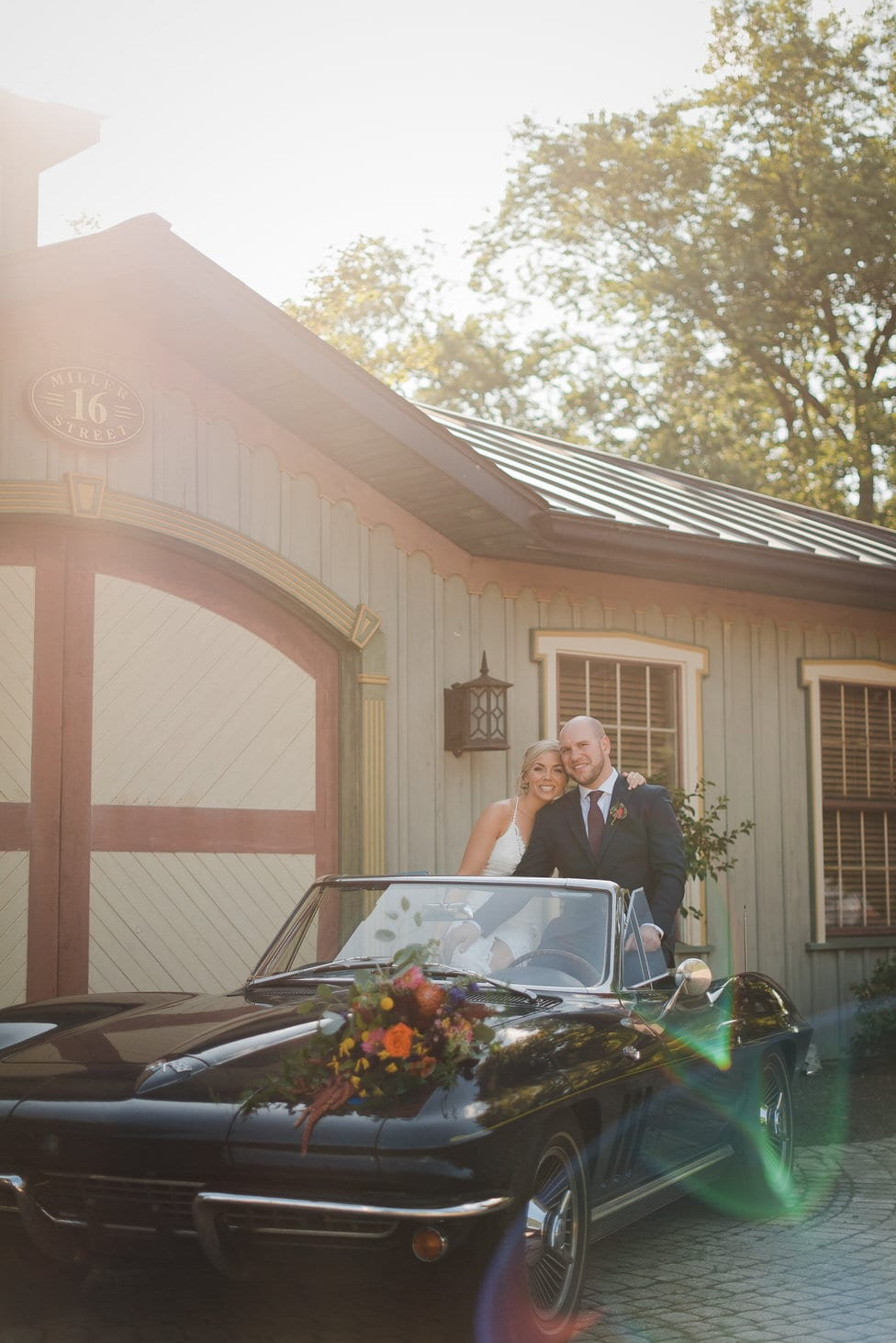 bride and groom sit together in antique convertible by fancy garage