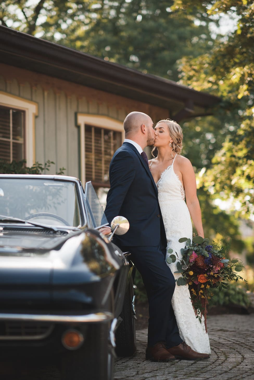 bride and groom kiss,  leaning against antique car
