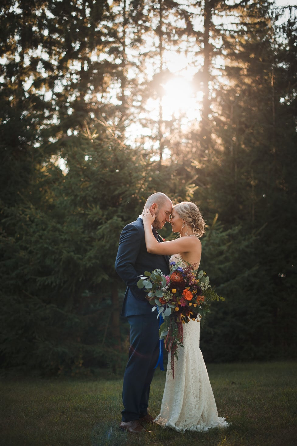 newlyweds stand in golden hour light coming through trees