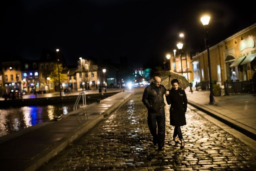 Mary and Adam walk along the cobble stone streets of Fells Point for a rainy evening engagement session.