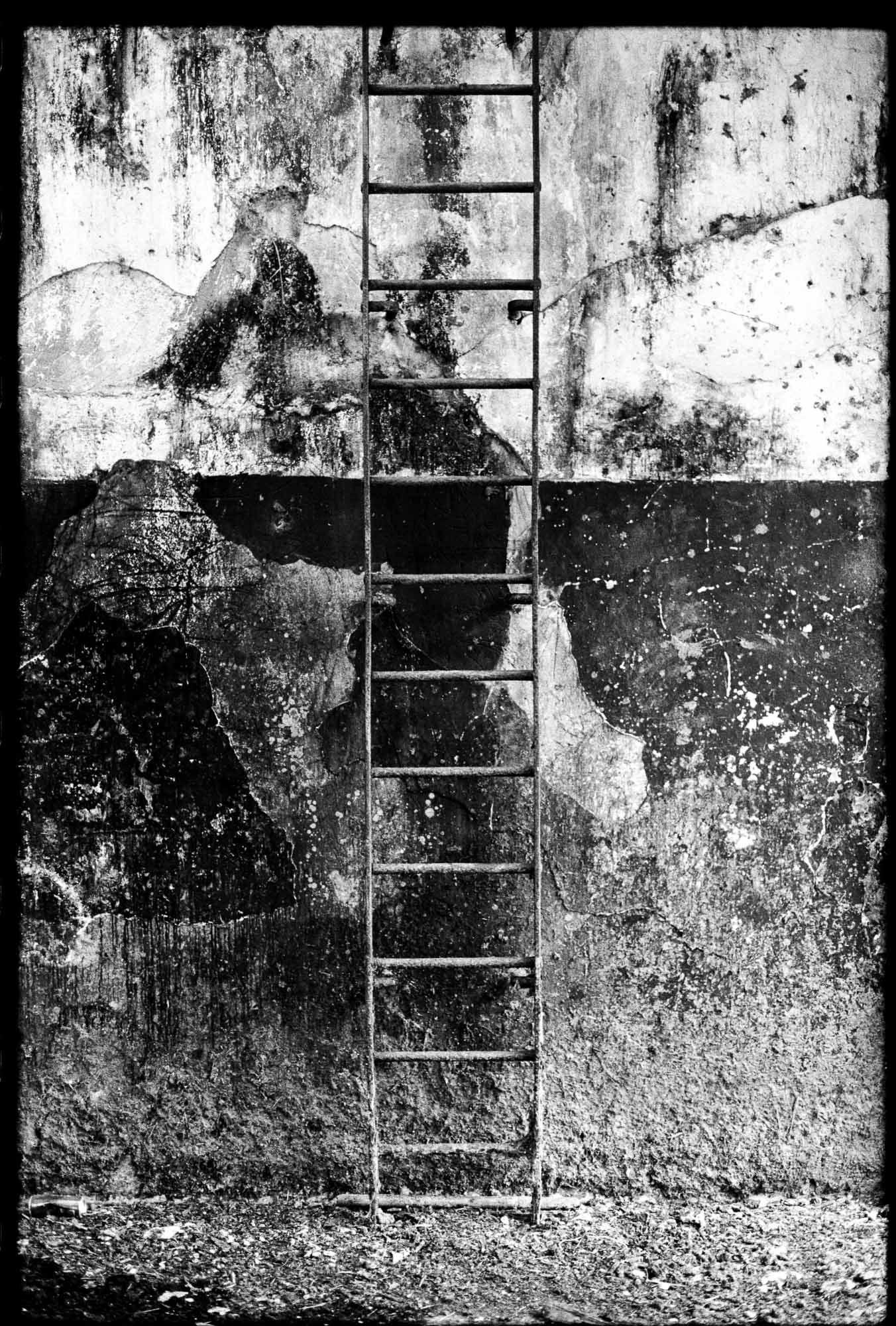 A decayed metal ladder bolted to the wall, shot in black and white using a Canon AE1-P