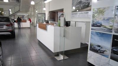 Autohaus Empfangsbereich Kombination in Hochglanz Weiß Nussbaum Dekor und Edelstahlsockel